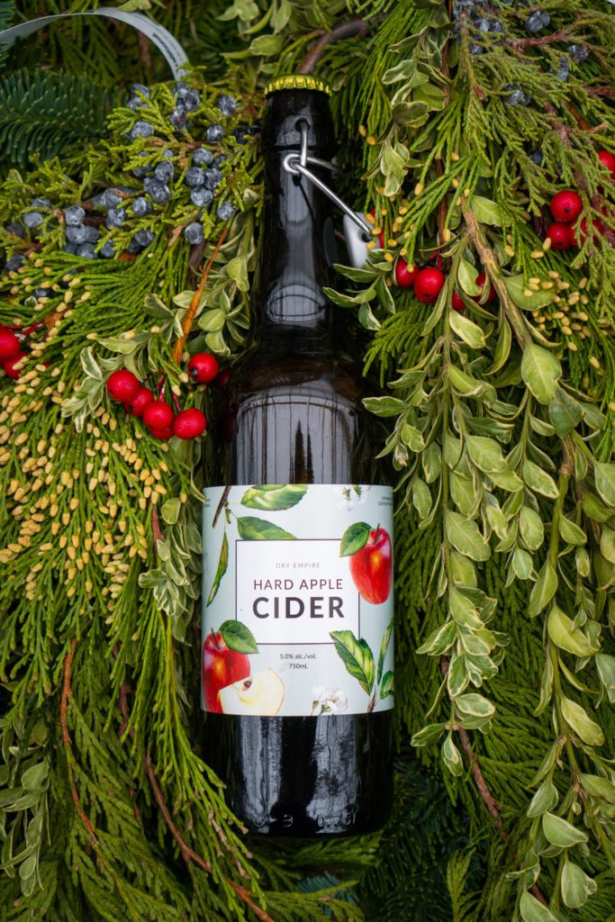 apple cider in bottle surrounded by greenery with white label