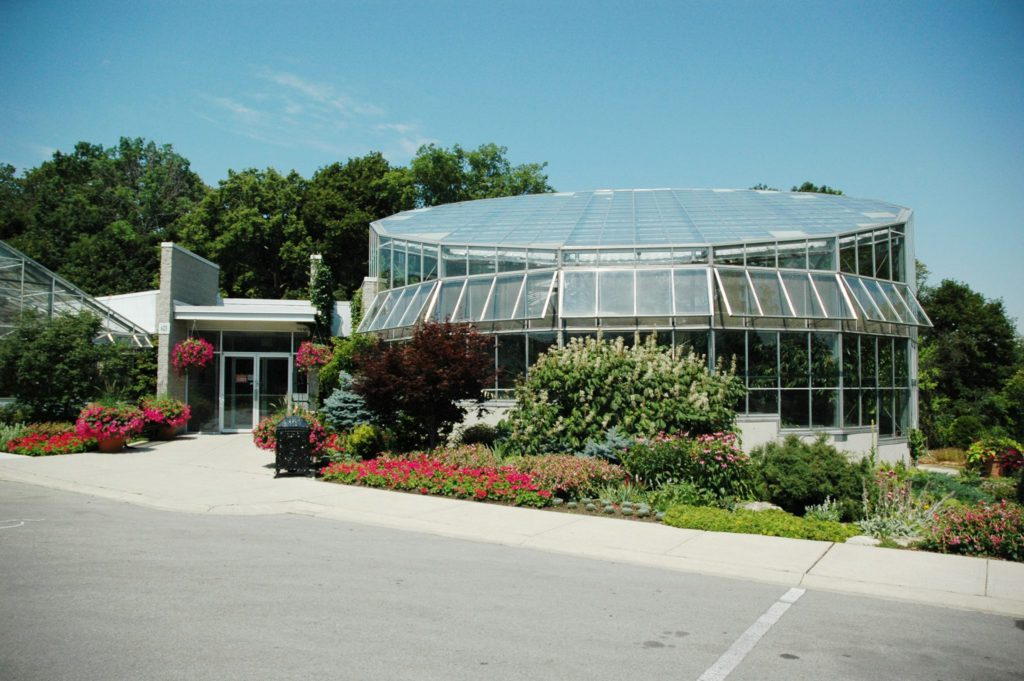 exterior view of large dome style greenhouse with nice garden surrounding
