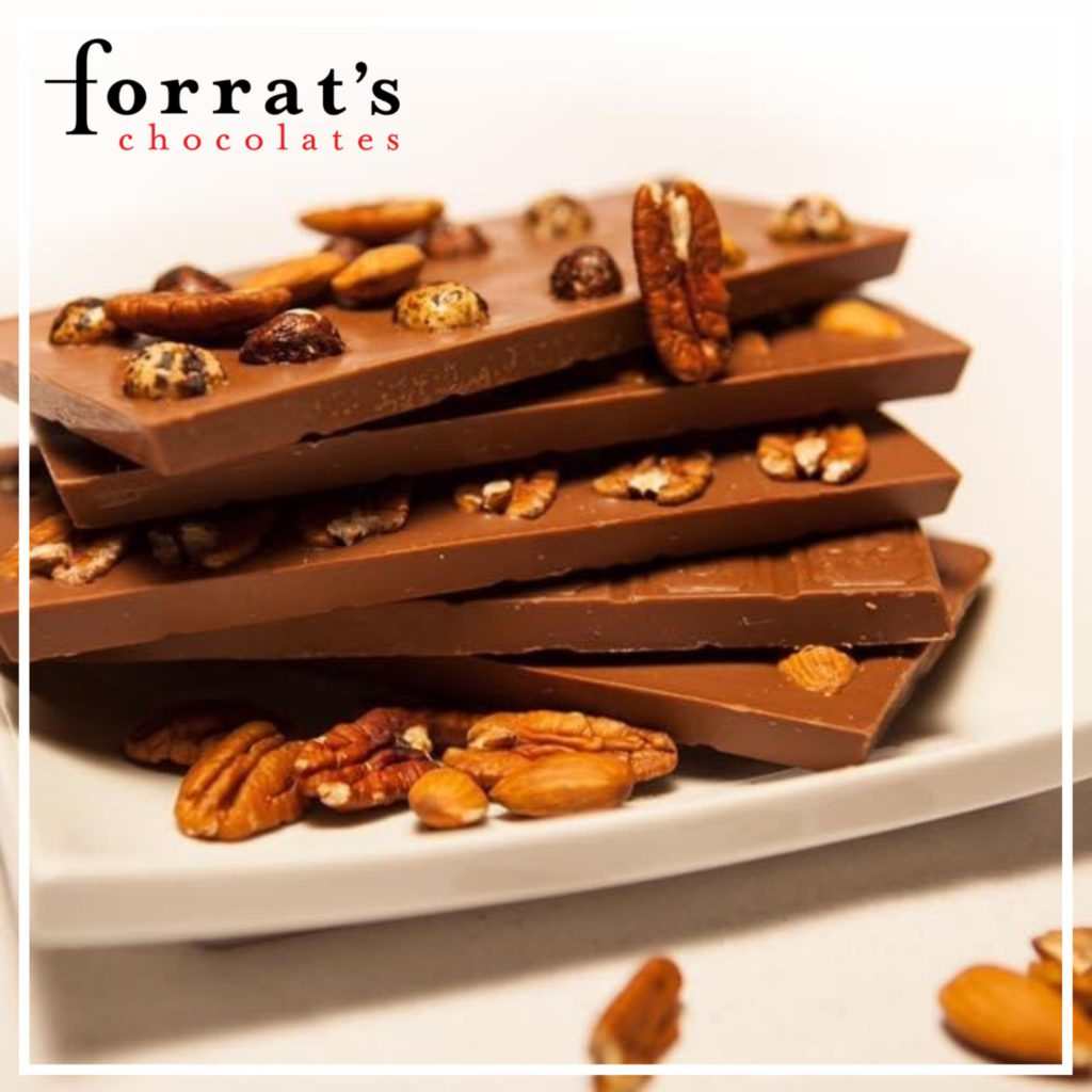 stack of chocolate fudge with nuts on a white plate with brand name in top left corner