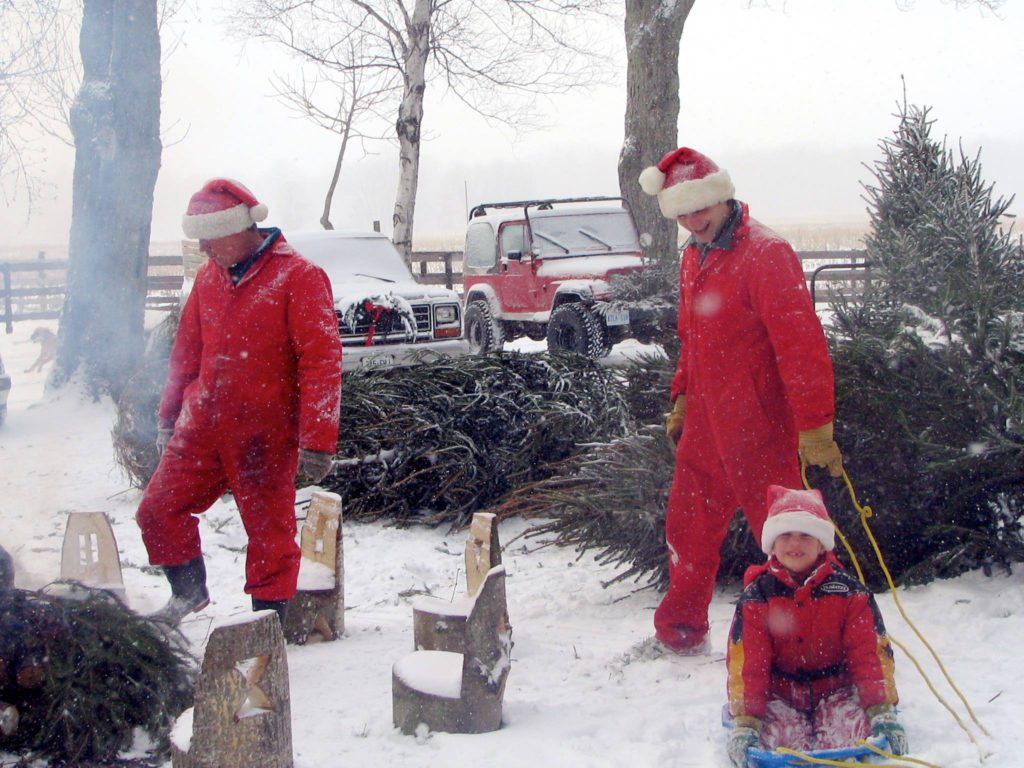 three people in red snowsuits one younger and sitting down pulling chopped christmas trees