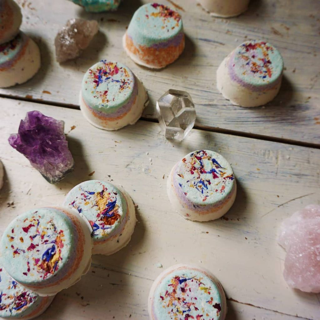 close up of pastel coloured bath bombs on wooden table