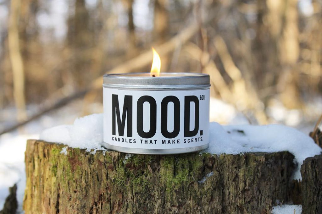 small candle lit with the word mood written on the front sitting on a snowy log in front of forestry