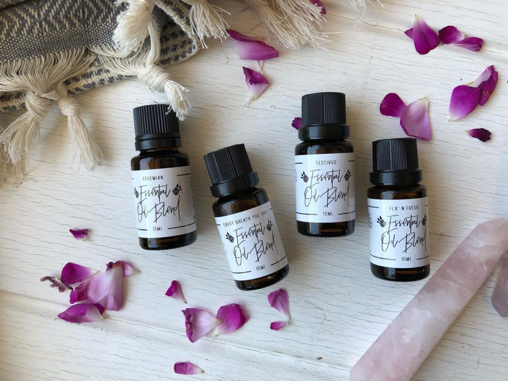 flat lay of small essential oil bottles with white labels on a table with purple flowers laid around on top