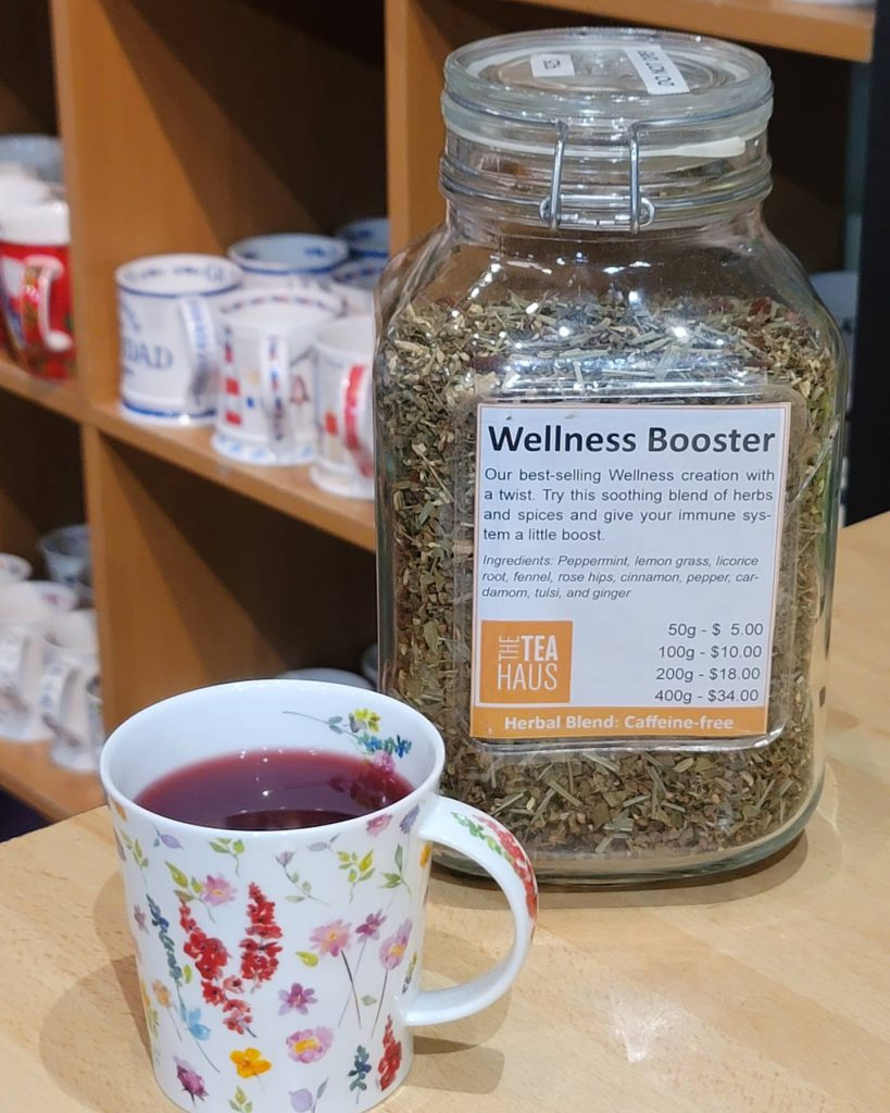 glass jar of loose leaf tea with white label on the front with a brewed tea in a mug to the left in front of product shelves