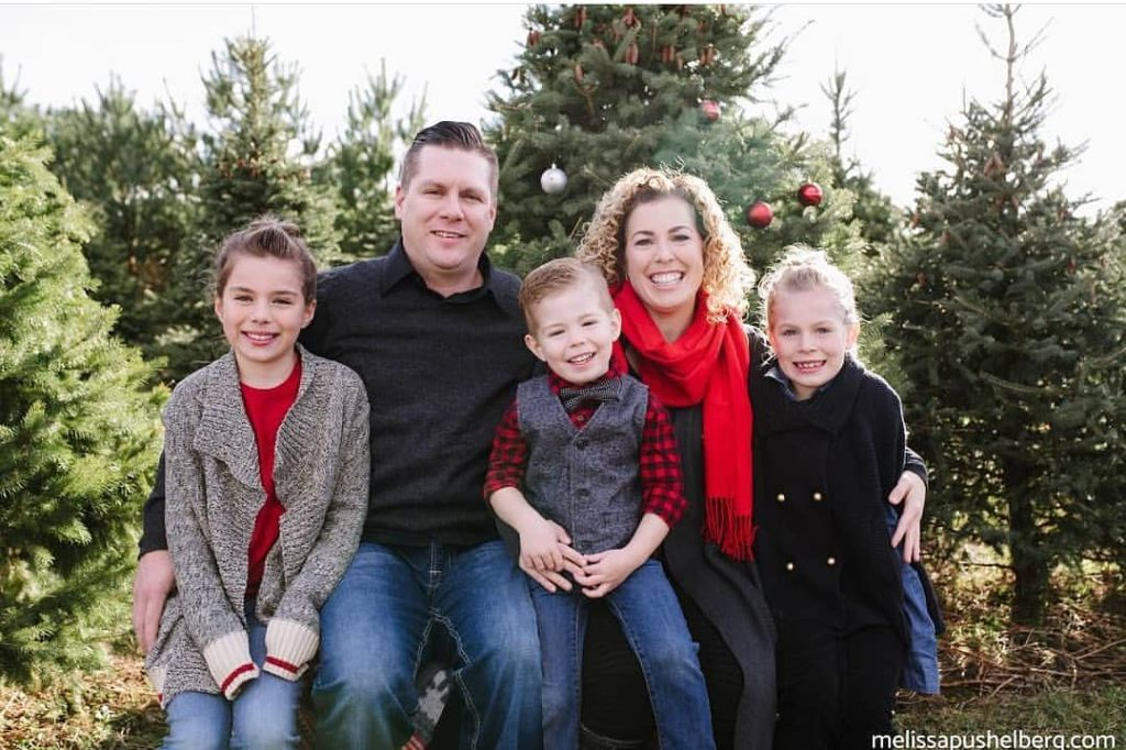 family sitting for family photos at christmas tree farm wearing red accents