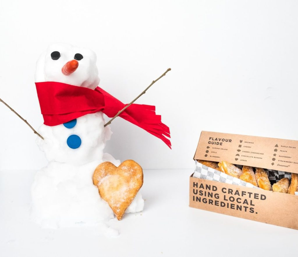 branded box of cookies with miniature snowman holding one cookie wearing a scarf