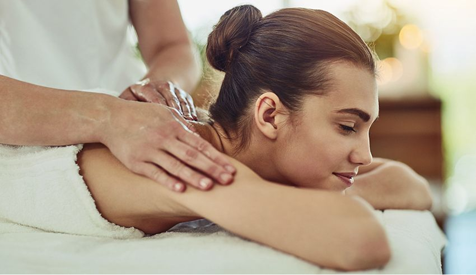 woman with brown hair at spa in massage bed with two hands rubbing her shoulders