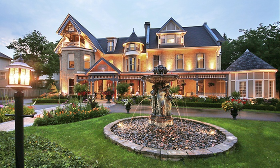 exterior view of beautiful colonial style buildling with many lights on outside with gazebo feature and large garden in front with large stone fountain going at dusk