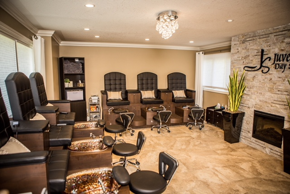 interior of salon style set up with large massage chairs and small tubs for feet with rolly stools at each chair end with some plants around and a lot of beige and brown accents