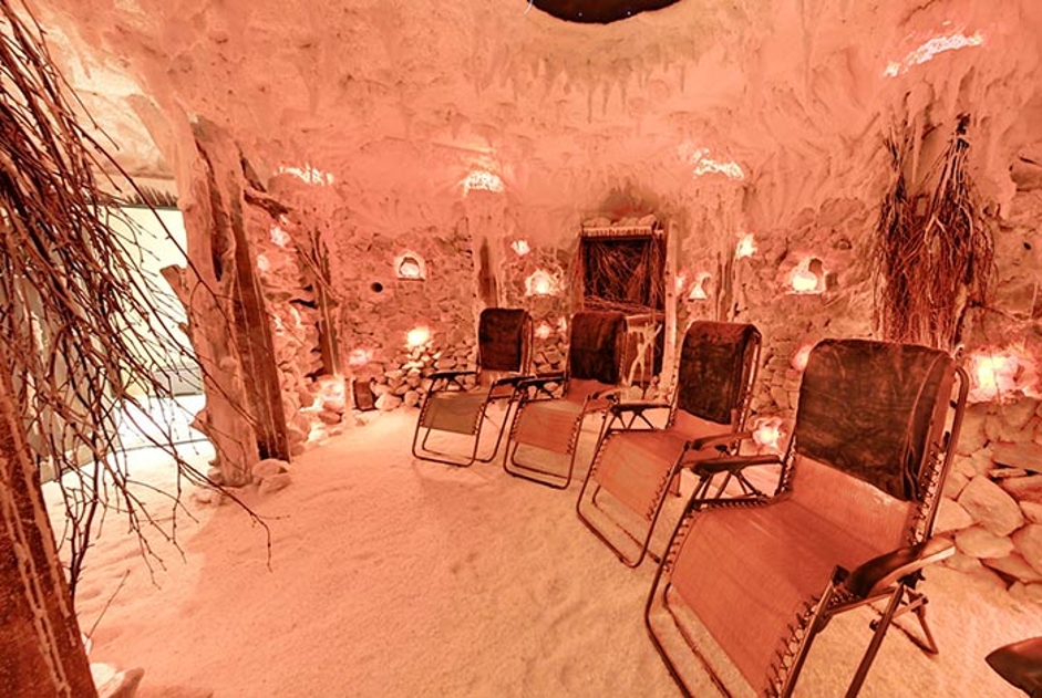 interior of clay salt room with orange accents and lawn loungers inside that can recline with sand for floor