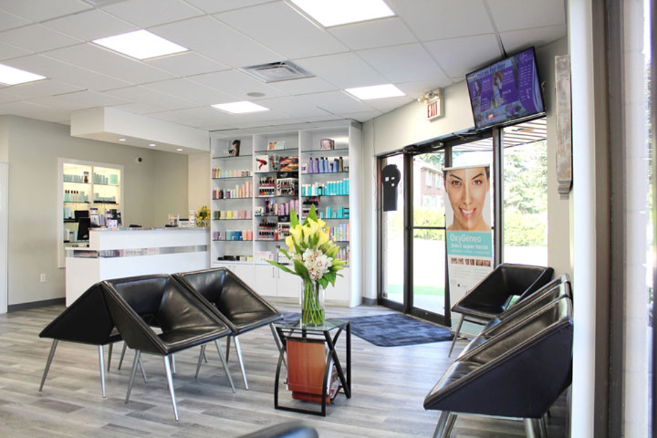 interior view of spa foyer with traingular leather seats in groups around the room and shelving with beauty products and tv in right hand corner of room
