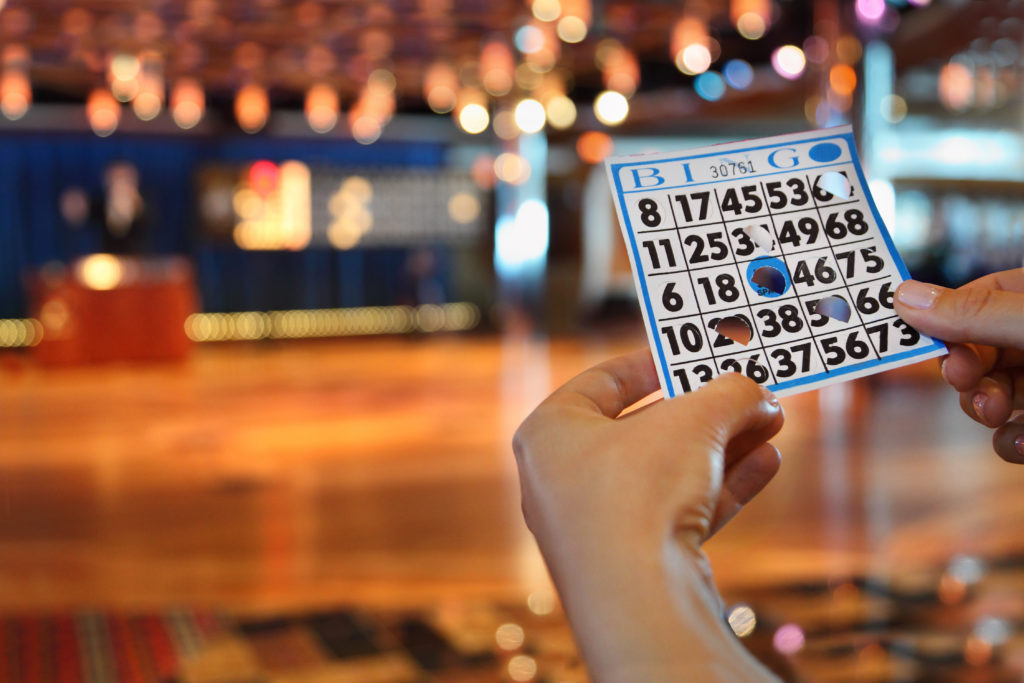 Hands hold bingo card with holes with blurred bar background