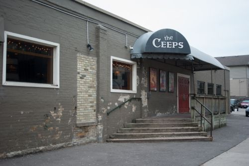 exterior of bar with large awning with brand on top with stairs leading to the front door