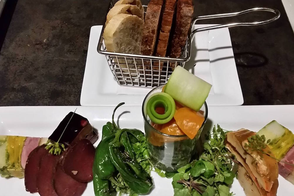 top view of charcuterie on white plate with various meat cheese and vegetables with a side plate of toasted bread in a wire mini basket