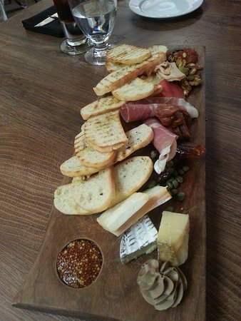 top view of charcuterie wooden board with various meat and cheese with sauce for dipping and glasses with beverages on the table