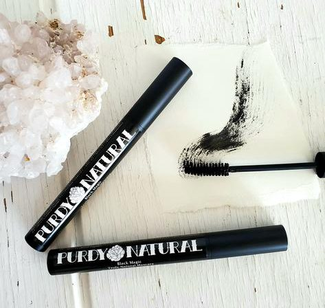 two bottles of mascara with one wand exposed with various gem detailing on a white background