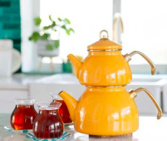 view of kitchen with large yellow double barreled tea pot on counter with three glasses of tea on a bright day