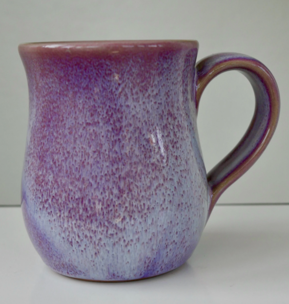 unique shaped coffee mug with purple speckles which fade towards the bottom on a white backround