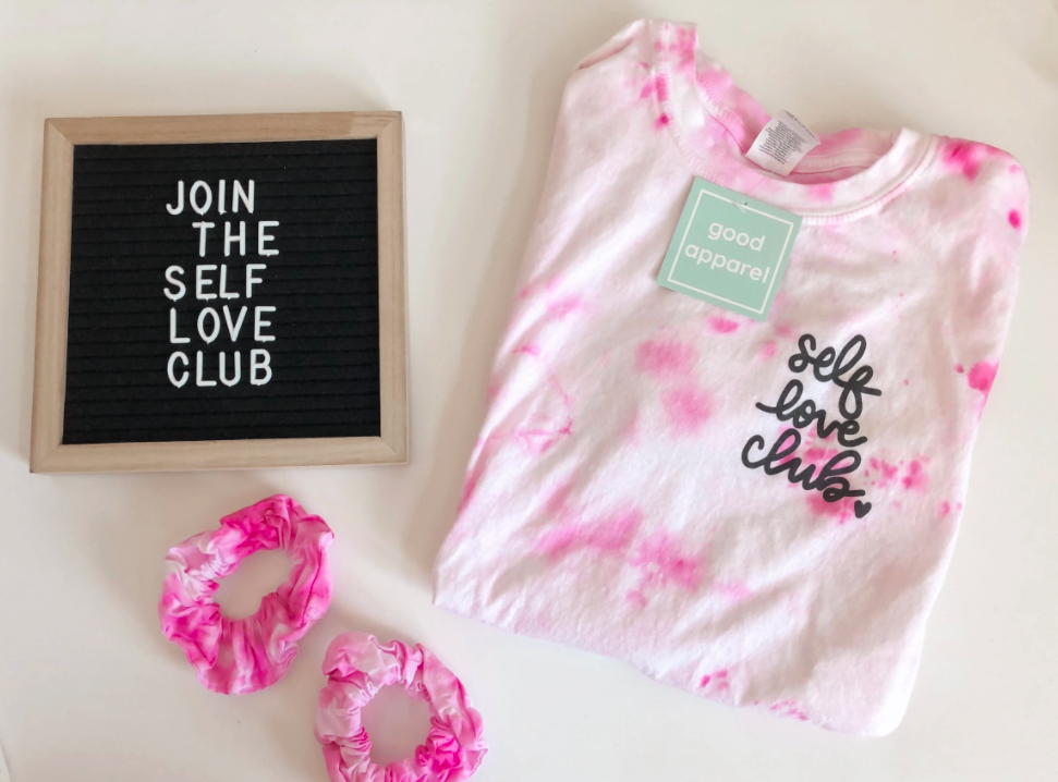 pale tie dye pink sweater with set of two similar scrunchies with a letterboard that says join the self love club on a white background