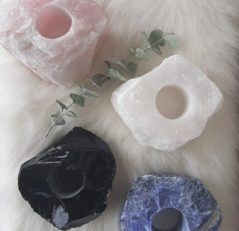 set of four different coloured candle holders made of salt on fur fabric beside a plant leaf