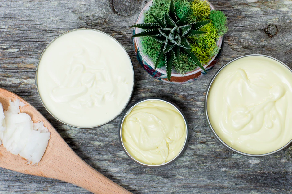 small tubs of body lotions with a wooden ladel holding lotion with a plant against a wooden background