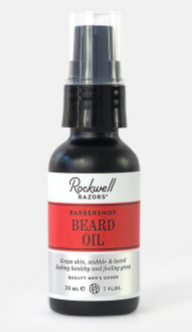 small container of beard oil with spray cap and red labelling against a white background