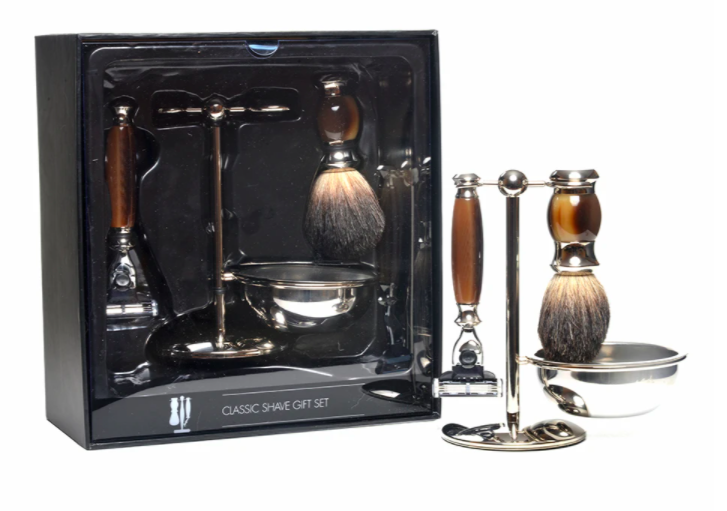 mens four piece shaving kit on display with brushes, razors, and handle sitting outside of box against a white background