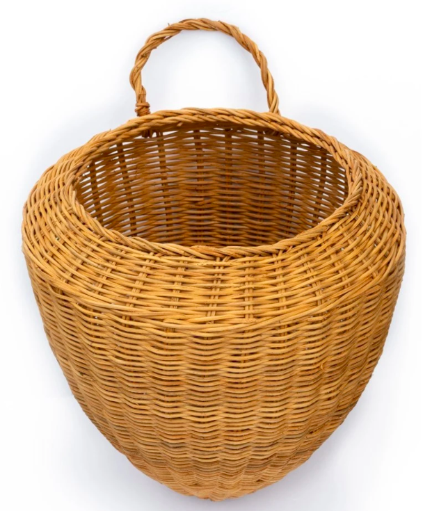 large wicker basket with one handle to far side and becomes cone shape towards the bottom