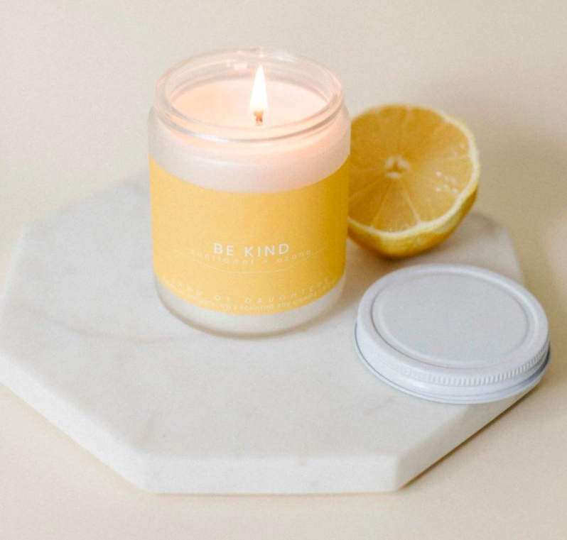 lit candle with yellow label sitting on marble coaster beside a lemon
