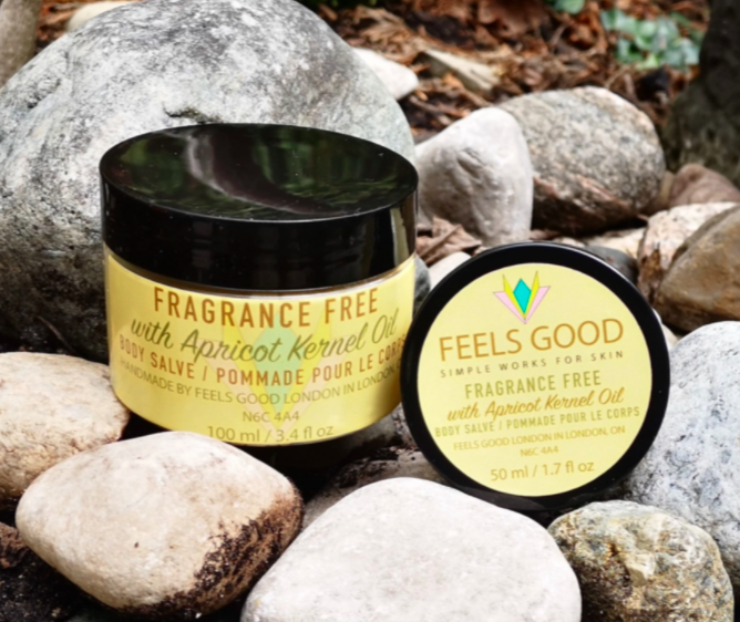 two small round bottles of body salve with yellow labelling sitting amongst rocks outside