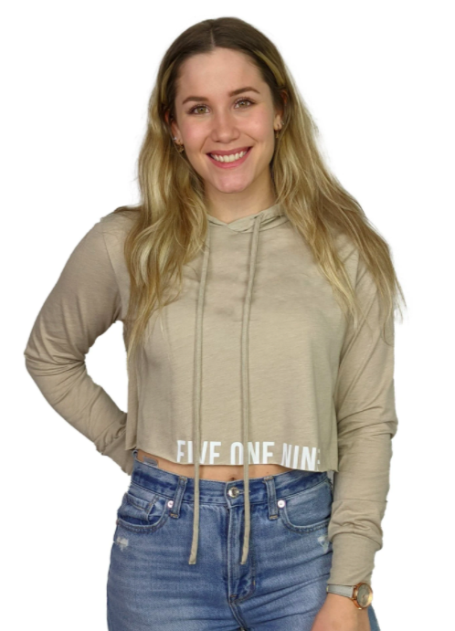 woman smiling at camera wearing a beige cropped hoodie with logo and branding in white along the bottom crop