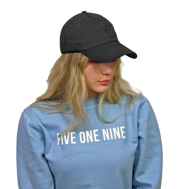 woman modelling a black hat with black embroidery on the front looking down wearing a blue sweater