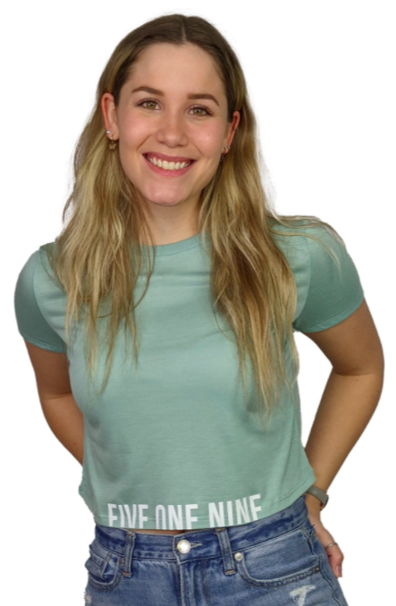 woman smiling at camera modelling a cropped t-shirt with branding in words along the waist