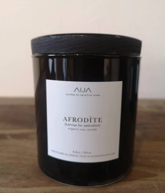 small black candle with white product label on the front sitting on a wooden counter