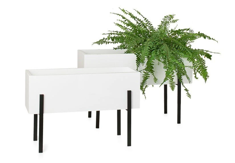 set of two large rectangular planter pots with long black legs and one fern in the planter to the right
