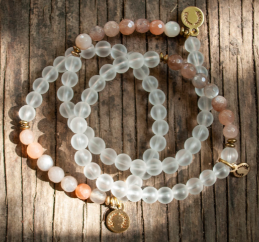 set of three stacker bracelets with golden pendants on each with clear and light pink beads