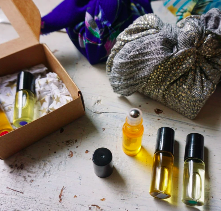 various boxes and knick knacks with small roller bottles of yellow substances inside on a white wooden counter