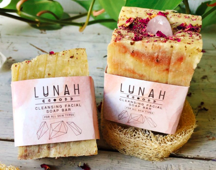 two pieces of soap in imperfect shapes with flower petals throughout the soap with branded label on the front sitting in front of a plant