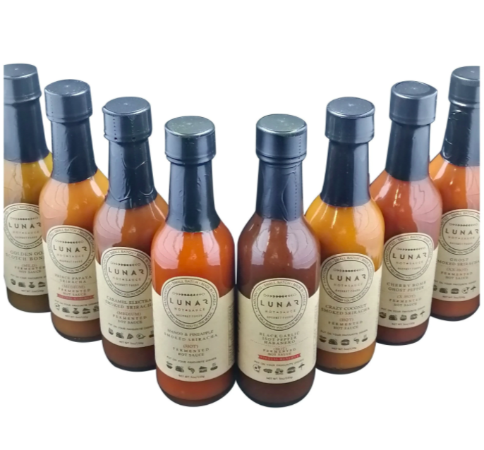 many hot sauce bottles lined up in a v with blue packaging on the lid and product details on labels