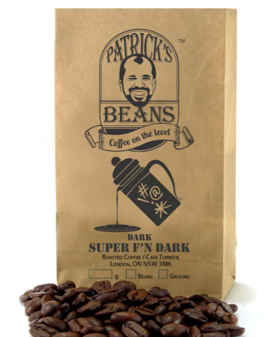 small brown paper bag of whole coffee beans with some displayed in front of the bag