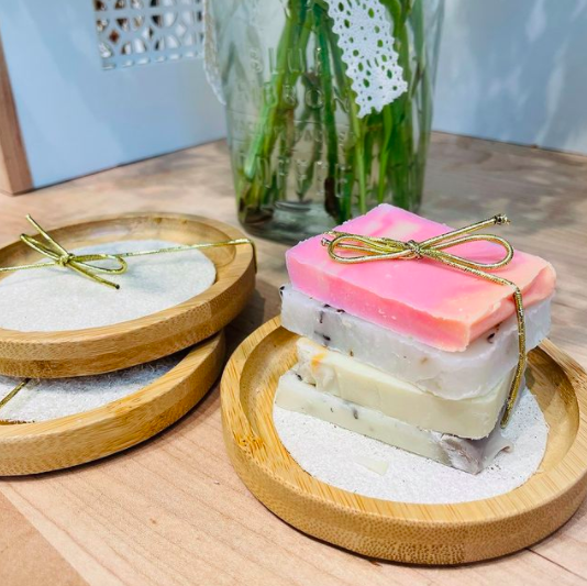 set of three soap dishes with one that has a package set of four handmade soaps with a plant in the background