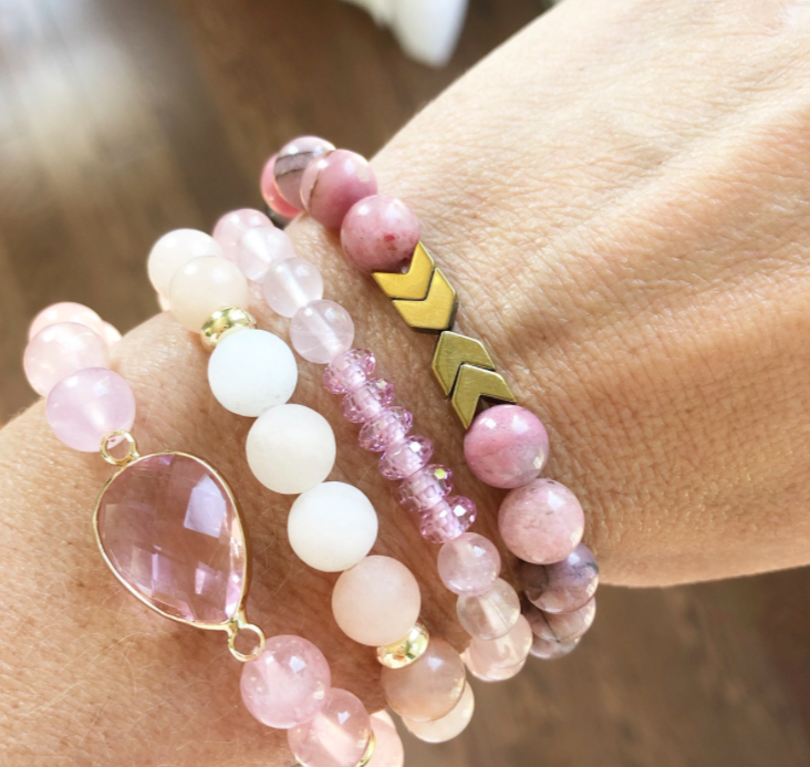wrist with a set of four pink stacker bracelets with various shapes and colours throughout