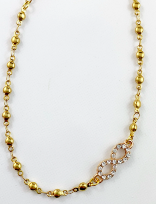 gold anklet with different sized beads and infinity jewel/pendant offset on the right side against a white background