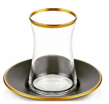 small glass tea cup with gold rim on a black saucer with gold rim