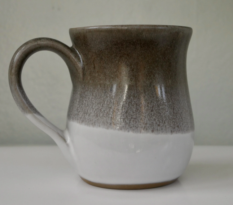 close up view of a coffee mug with brown on the top which fades into white at the bottom against a white background