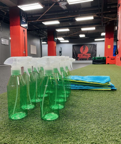 Interior of a gym facility with various pieces of workout equipment, spray bottles and cloths sitting on astro turf flooring