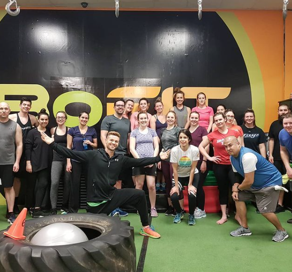 group of people working out posing for a photo with astro turf for flooring