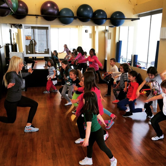 Interior of a gym facility with various pieces of workout equipment with a childrens class happening and one woman instructor at the front