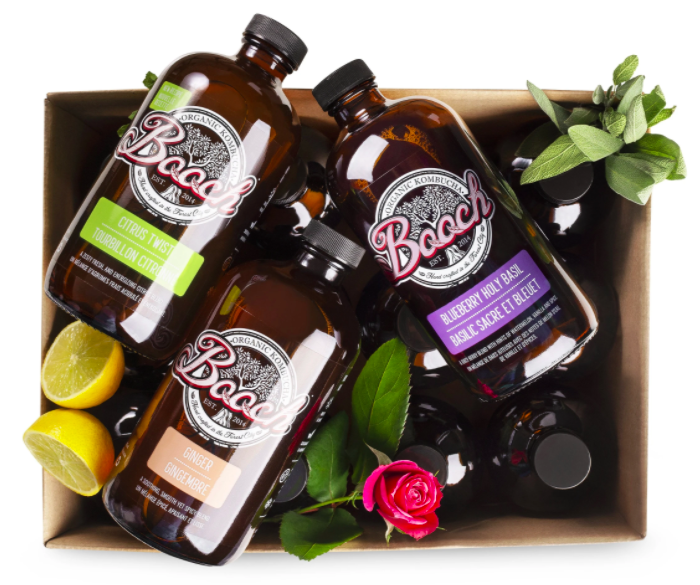 set of three glass bottles with different coloured branding on the front in a box amongst fresh lemon, herbs, and roses