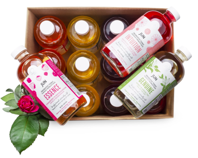 Boxed set of kombucha in glass bottles with three bottles outside of box with labels up in different colours with a rose